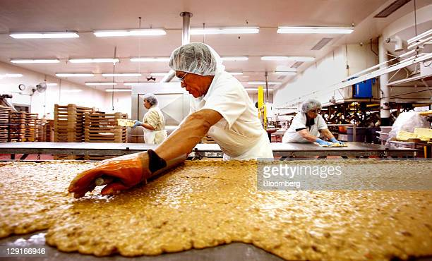 See's Candies Inc employee Jose Rodriguez rolls peanut crunch onto a cooling slab at the company's factory in San Francisco California US on Monday...