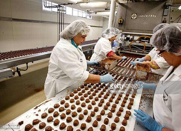 See's Candies Inc. Employees add the final touches on top of chocolate truffles at the company's factory in San Francisco, California, U.S., on...