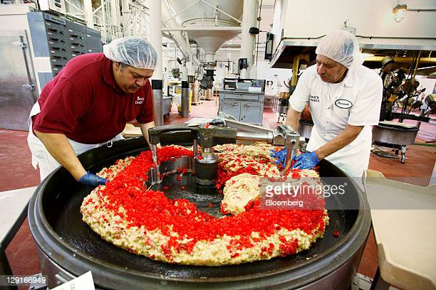 See's Candies Inc. Employees Bobby Mauricio, left, and Fernando Garcia help mix cherries into the mayfair cream candy at the company's factory in San...