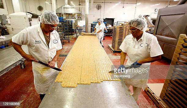 See's Candies Inc. Employees Jose Vallejo, left, and Jose Rodriguez, right, cut peanut crunch into pieces at the company's factory in San Francisco,...