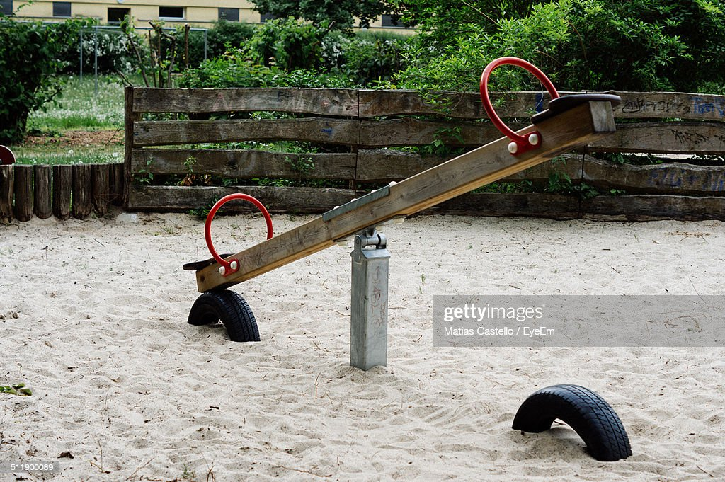 Seesaw in an empty playground with old fence in the background : Stock Photo