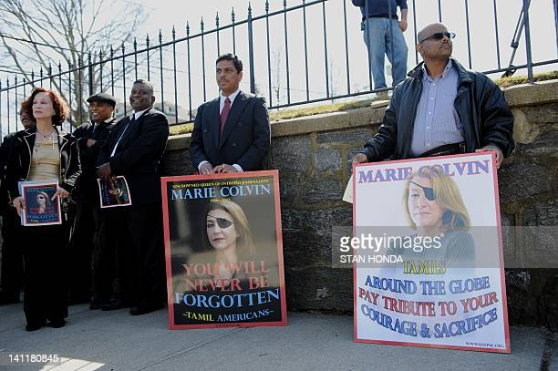 Seetharams Sivam and Varatharajah Suppiah and other members of the Tamil American community hold signs of support after the funeral of slain Times of...