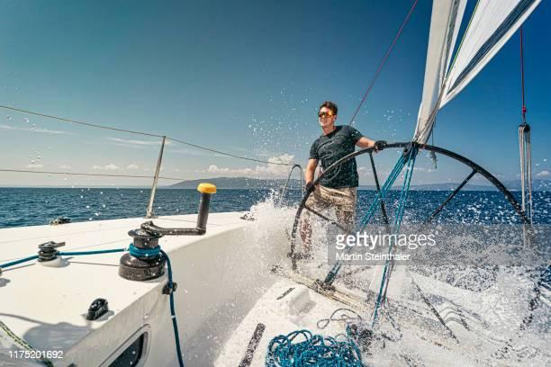 segelboot mit segler am offenen meer - welle bricht wasser spritzt - yachting stock pictures, royalty-free photos & images