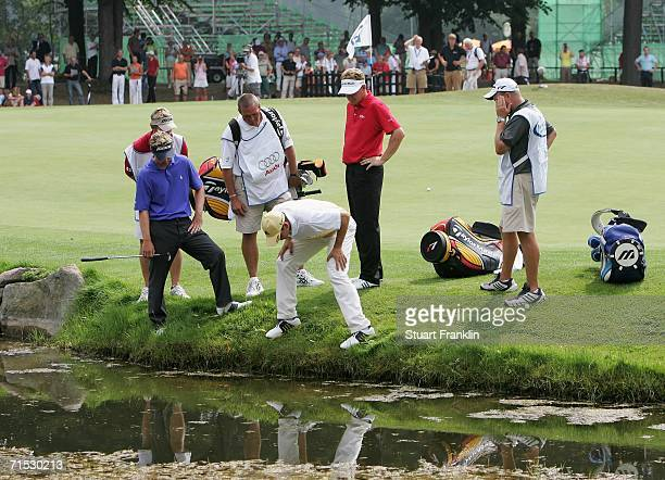 Segio Garcia of Spain is helped by his playing partners Luke Donald and Paul Broadhurst and caddies as they search for his ball in the bank by the...