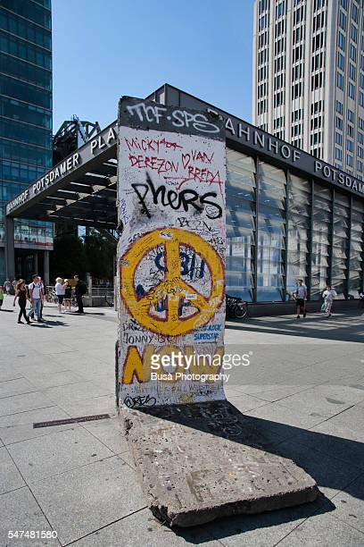 Segment of the Berlin Wall covered in graffiti with peace symbol, in Potsdamer Platz, Berlin, Germany