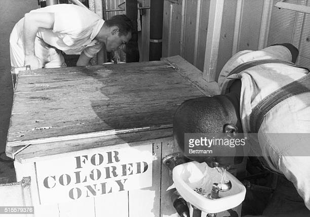 Segregated drinking fountain in use in the American South Undated photograph Sign reads 'For colored only'