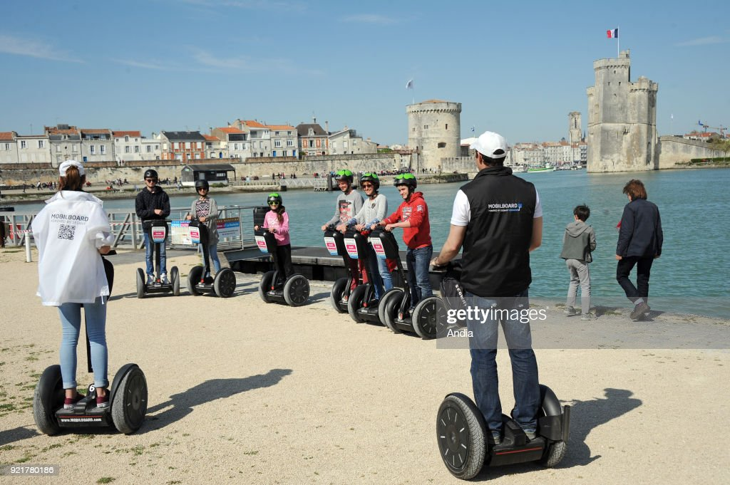 Segway city tour in La Rochelle (western France). In the background, the towers 'tour de la Chaine' and 'tour Saint-Nicolas' at the entrance to the Old Harbour.