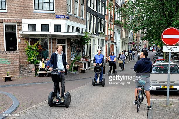 segway tour along a canal in amsterdam - segway stock pictures, royalty-free photos & images