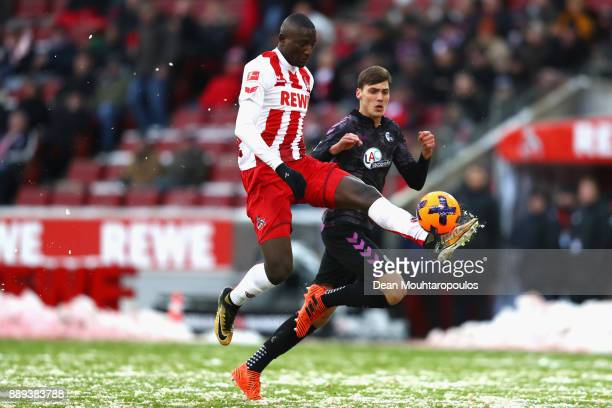 Sehrou Guirassy of FC Koeln is tackled by Pascal Stenzel of SC Freiburg during the Bundesliga match between 1 FC Koeln and SportClub Freiburg at...