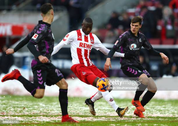 Sehrou Guirassy of FC Koeln is tackled by Robin Koch and Pascal Stenzel of SC Freiburg during the Bundesliga match between 1 FC Koeln and SportClub...