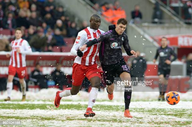 Sehrou Guirassy of Koeln and Pascal Stenzel of Freiburg battle for the ball during the Bundesliga match between 1 FC Koeln and SportClub Freiburg at...