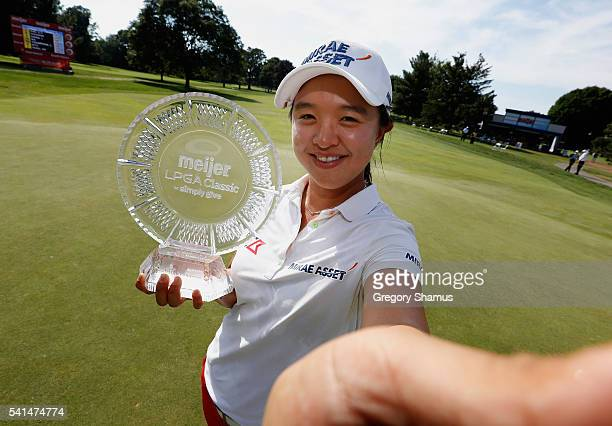 Sei Young Kim of South Korea poses for a simulated selfie with the championship trophy after winning the Meijer LPGA Classic on the first playoff...
