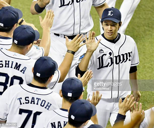 Seibu Lions ace Takayuki Kishi exchanges highfives with teammates after a 30 win over the Nippon Ham Fighters at Seibu Prince Dome in Saitama...