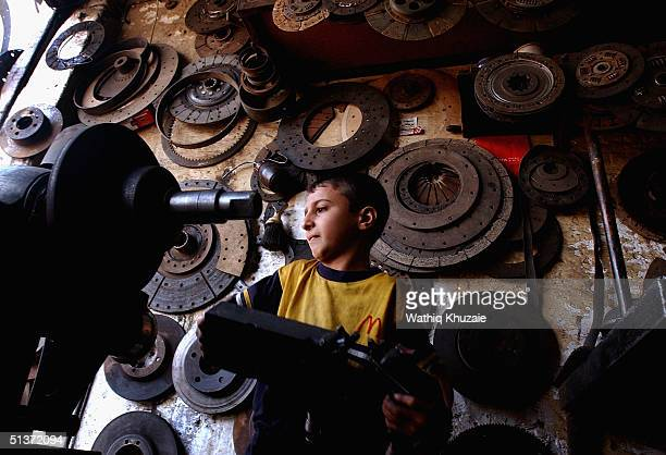 Seif Salah works in an automobile mechanic shop September 29 2004 in Baghdad Iraq The boy will earn around four US dollars a week for his work War...