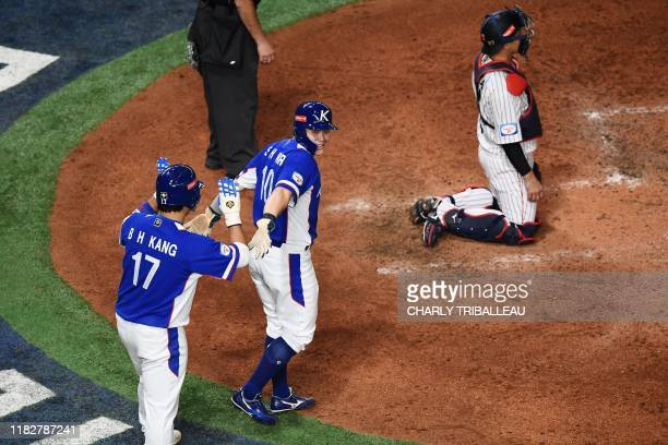 Seihyok Park of South Korea is congratuated by teammate Baekho Kang during the WBSC Premier 12 Super Round baseball match between Japan and South...