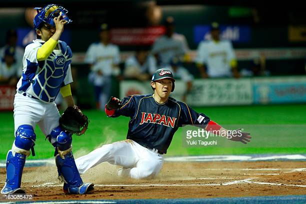 Seiichi Uchikawa of Team Japan slides safely into home to tie the game in the top of the eighth inning during Pool A Game 1 between Team Japan and...