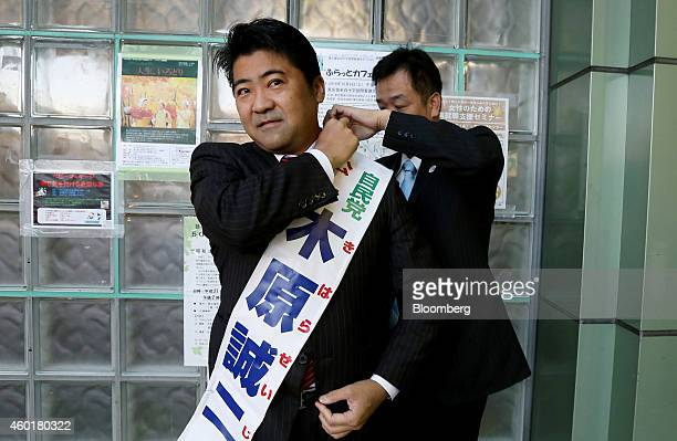 Seiji Kihara a candidate for the Liberal Democratic Party wears a sash bearing his name during his national election campaign at a train station in...