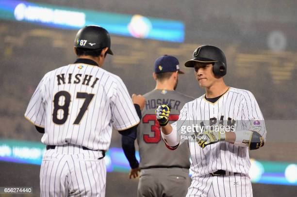 Seiji Kobayashi celebrates a single with coach Toshihisa Nishi in the third inning against team United States during Game 2 of the Championship Round...