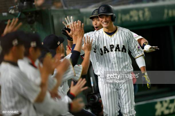 Seiji Kobayashi of Team Japan is greeted in the dugout after hitting a tworun home run in the second inning during Game 6 of Pool B against Team...