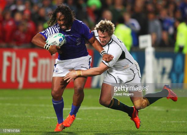 Seilala Mapusua of Samoa is tackled by Jean de Villiers of the Springboks during the IRB 2011 Rugby World Cup Pool D match between South Africa and...