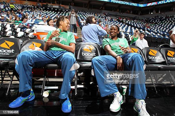 Seimone Augustus and Amber Harris of the Minnesota Lynx relax on the sidelines before the game against the Atlanta Dream in Game One of the 2011 WNBA...