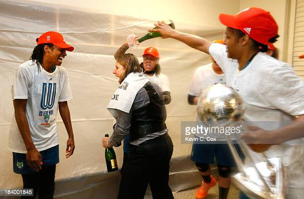 Seimone Augustus and Maya Moore douse champagne on head coach Cheryl Reeve of the Minnesota Lynx as they celebrate their 8677 win over the Atlanta...