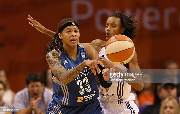 Seimone Augustus of the Minnesota Lynxpasses the ball under pressure from DeWanna Bonner of the Phoenix Mercury during game three of the WNBA Western...