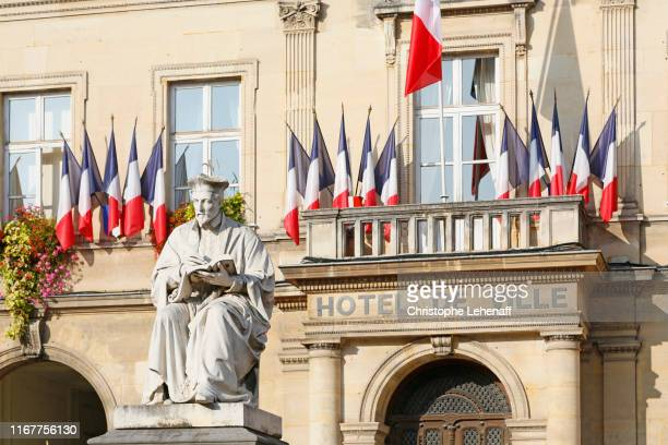 seine et marne. melun. downtown. facade of the hotel de ville. in the foreground statue representing jacques amyot (prelate and one of the most renowned translators of the renaissance). - town hall stock pictures, royalty-free photos & images