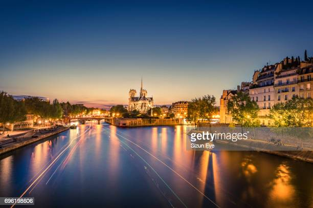 Seine riverfront with Notre-Dame Cathedral and boat light trails on the water at sunset in Paris, France.