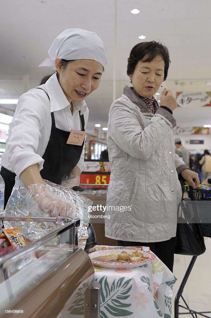 A Seiyu GK employee recommends a cooked pork sample to a customer in the company's supermarket in Tokyo, Japan, on Wednesday, Nov. 14, 2012. Seiyu GK is a unit of Wal-Mart Stores Inc. Photographer: Akio Kon/Bloomberg via Getty Images