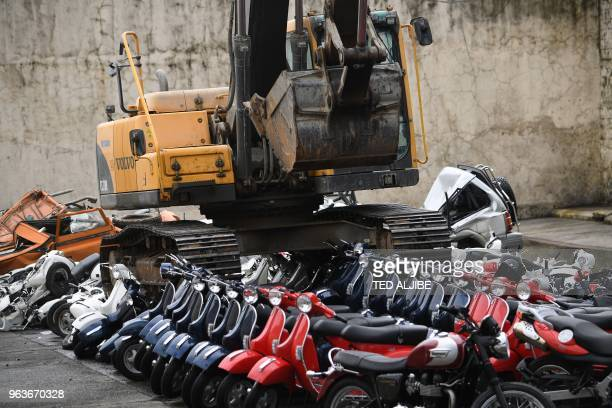 TOPSHOT Seized vehicles and motorcycles are destroyed during a ceremony attended by President Rodrigo Duterte at the customs yard in Manila on May 30...