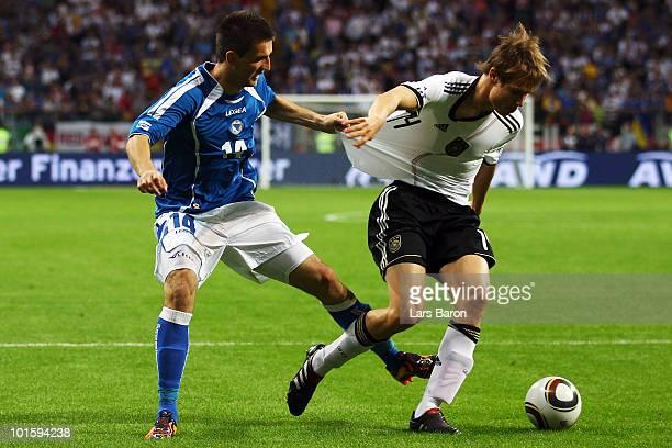 Sejad Salihovic of Bosnia challenges Holger Badstuber of Germany during the international friendly match between Germany and BosniaHerzegovina at...