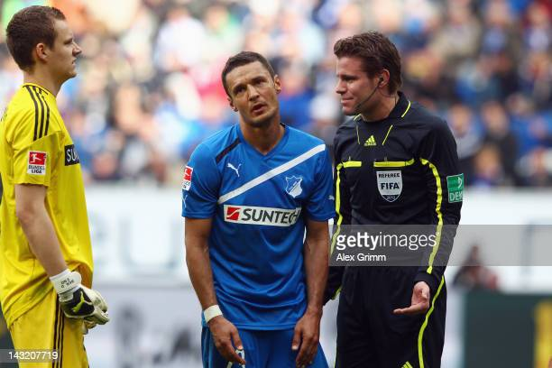 Sejad Salihovic of Hoffenheim reacts as he stands between referee Felix Brych and goalkeeper Bernd Leno of Leverkusen during the Bundesliga match...