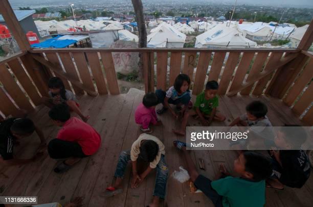 Sejumlah anak bermain dengan latar belakang tenda-tenda tenda penampungan sementara korban bencana yang mulai rusak di Kelurahan Balaroa, Palu,...