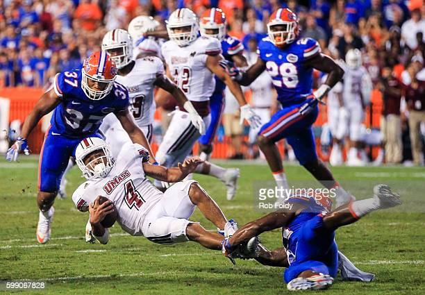 Sekai Lindsay of the Massachusetts Minutemen is tackled during the second half of the game against the Florida Gators at Ben Hill Griffin Stadium on...