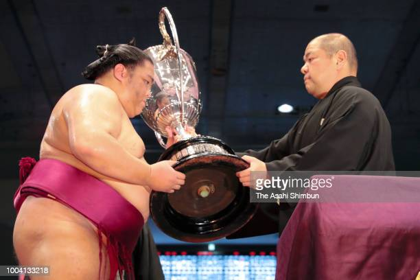 Japan Sumo Association President Hakkaku and high ranked sumo wrestlers observe a minute of silence for the victims of the Western Japan Torrential...