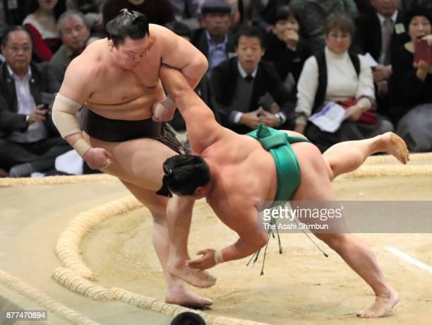 Sekiwake Yoshikaze pushes Mongolian yokozuna Hakuho out of the ring to win during day eleven of the Grand Sumo Kyushu Tournament at Fukuoka...