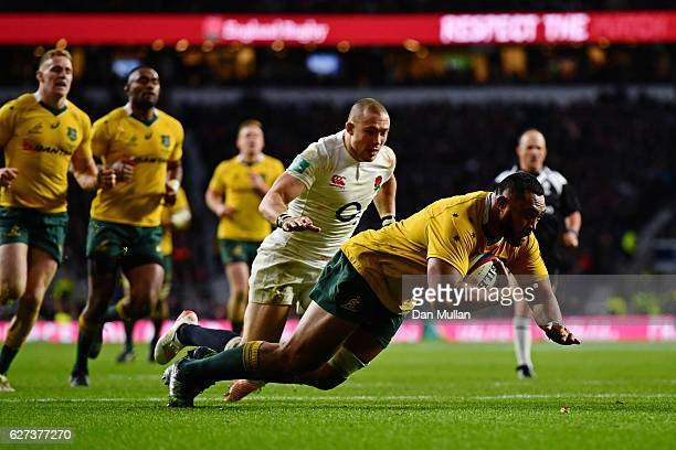 Sekope Kepu of Australia scores his sides third try as Mike Brown of England attempts to catch him during the Old Mutual Wealth Series match between...