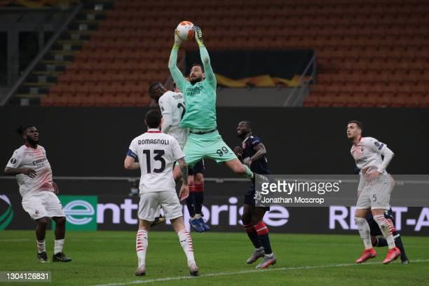 Sekou Sanogo of FK Crvena Zvezda looks on as Gianluigi Donnarumma of AC Milan leaps to gather the ball from a cross during the UEFA Europa League...