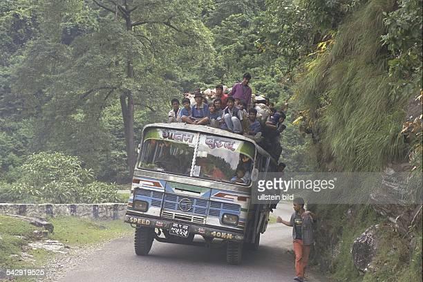 Selbst auf dem Dach eines vollbesetzten Reisebusses, der sich auf einer Landstraße in den Bergen Nepals unter seiner Last schwer neigt, haben die...