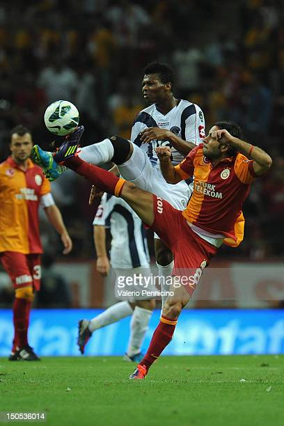 Selcuk Inan of Galatasaray AS competes with Kalu Uche of Kimpasa AS during the turkish Super League match between Galatasaray AS and Kimpasa AS at...
