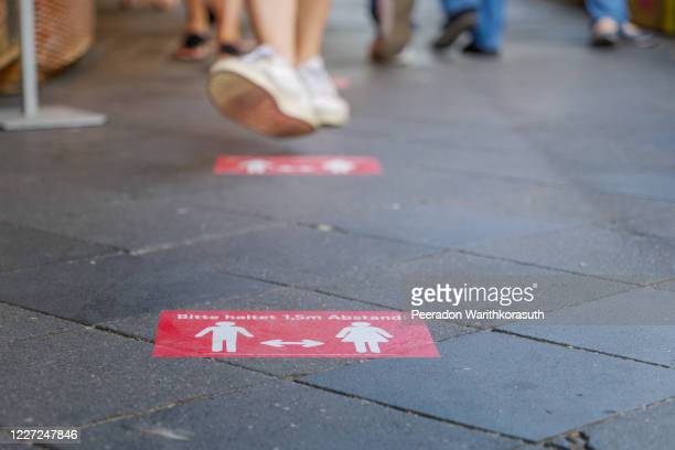 """selected focus at """" haltet 1.5m abstand """" means """" keep 1.5 m distance"""", on red rectangular caution sign on sidewalk outside supermarket in germany during social distancing by epidemic of covid-19. - lockdown stock-fotos und bilder"""