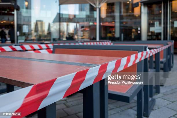 selected focus view at red and white caution tape restrict outdoor dining area of restaurant or cafe in düsseldorf, germany during lockdown by epidemic covid-19. - forbidden stock pictures, royalty-free photos & images
