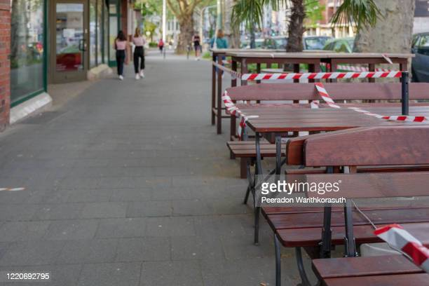 selected focus view at red and white caution tape wrapped around outdoor tables and seats area of cafe which closed during social distancing and global quarantine from epidemic of covid-19 virus. - lockdown stock-fotos und bilder