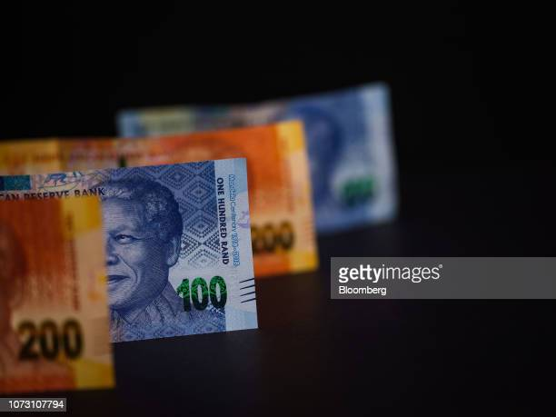A selection of 100 and 200 South African rand banknotes featuring an image of former South African President Nelson Mandela stand in this arranged...
