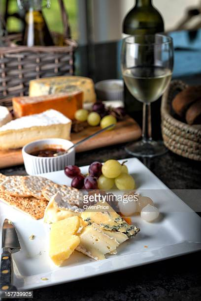 Selection of Cheese with chrackers grapes and pickle.