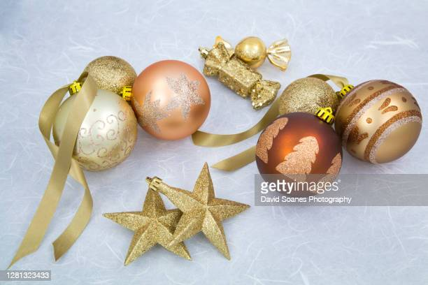 a selection of colourful christmas baubles against a grey background - david soanes stock pictures, royalty-free photos & images