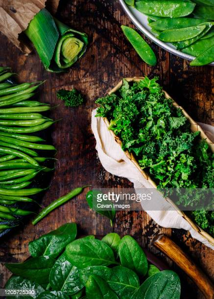 selection of fresh green organic vegetables on a wooden table - spinach stock pictures, royalty-free photos & images