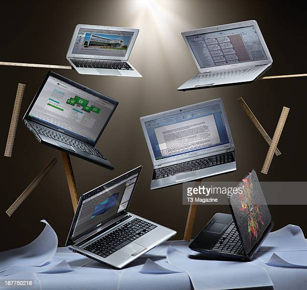 Selection of laptop computers surrounded by graph paper and rulers for an article on university-suitable laptops, including Apple MacBook 11-inch,...