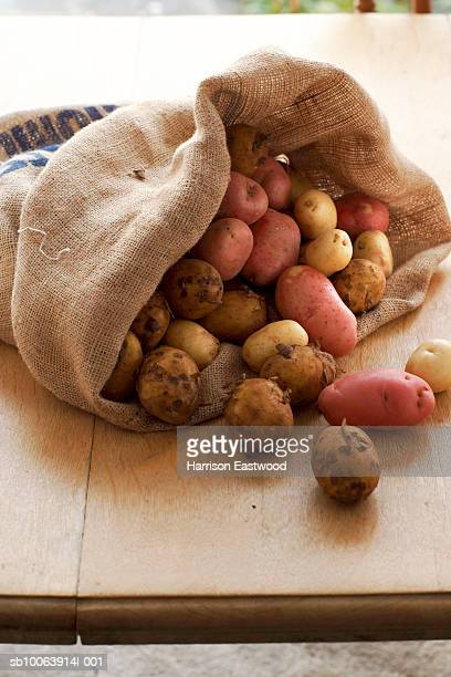 Selection of potatoes in sack on kitchen table